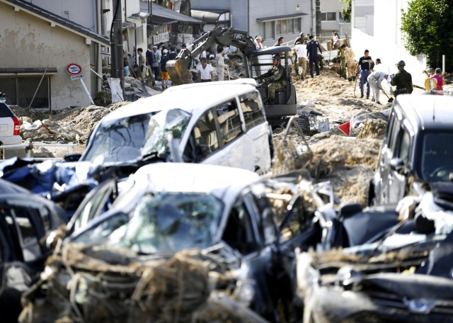 Cars are trapped in mud as residents clean up after days of heavy rain in Hiroshima city, southwestern Japan, on Tuesday, 10 July.