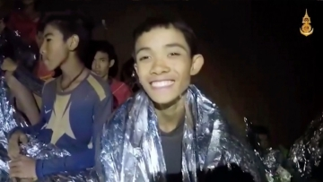In this image taken from video provided by the Royal Thai Navy Facebook Page, a Thai boy smiles as Thai Navy SEAL medic help injured children inside a cave in Mae Sai, northern Thailand.