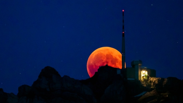 The moon turns red during a total lunar eclipse, behind the Saentis in Luzern, Switzerland, on Friday, 27 July.