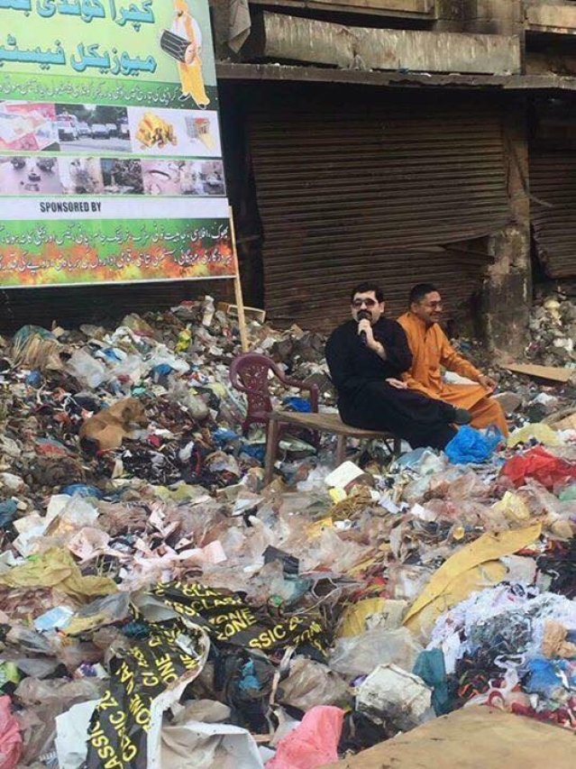 Motiwala campaigning for the elections on a pile of garbage.