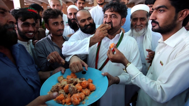 Supporters of Pakistani politician Imran Khan, offer sweets to each other to celebrate the victory of their party candidate, in Peshawar, Pakistan.