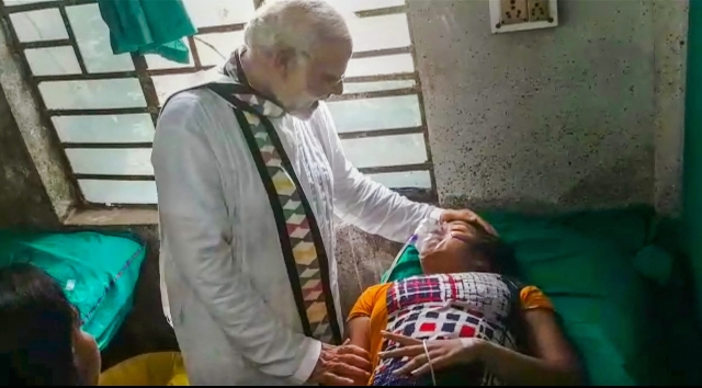 PM Modi meets a woman who was injured during his rally in Midnapore.