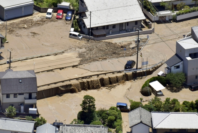 Mud waters cover the streets after the Enoki River running through the town overflowed, in Fuchu, Hiroshima prefecture, southwestern Japan, on Tuesday, 10 July.