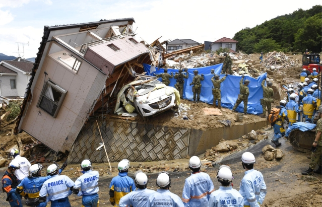 Rescuers conduct a search operation for missing persons in Kumano town, Hiroshima prefecture, western Japan, on Monday, 9 July.