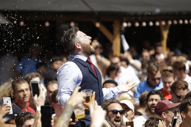 An England soccer fan dressed in a waistcoat to mimic England manager Gareth Southgate, is lifted up as fans gather to watch a live broadcast on a big screen of the quarterfinal match between England and Sweden at the 2018 soccer World Cup, in Flat Iron Square, south London, Saturday, July 7, 2018.