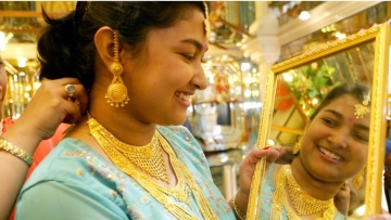 A young Indian woman tries gold ornaments on the occasion of the Hindu festival of Dhanteras. Image used for representation.