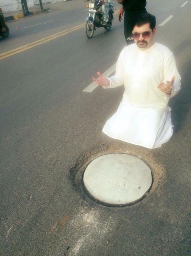 Motiwala sits next to a manhole.