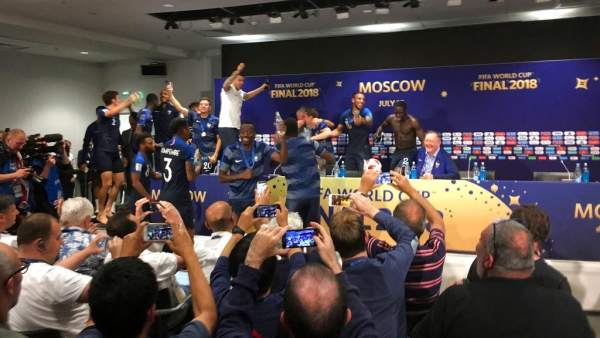 French players celebrate after bursting into a press conference by France head coach Didier Deschamps.