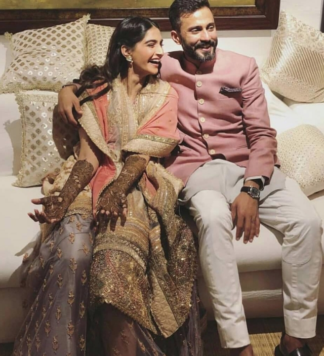 Anand Ahuja wore a rose pink sherwani coordinated by picking a greyish-lavendar pocket square to match Sonam's <i>lehenga</i> for the intimate mehendi.