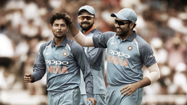 Kuldeep Yadav celebrates a wicket with Rohit Sharma as Virat Kohli looks on.