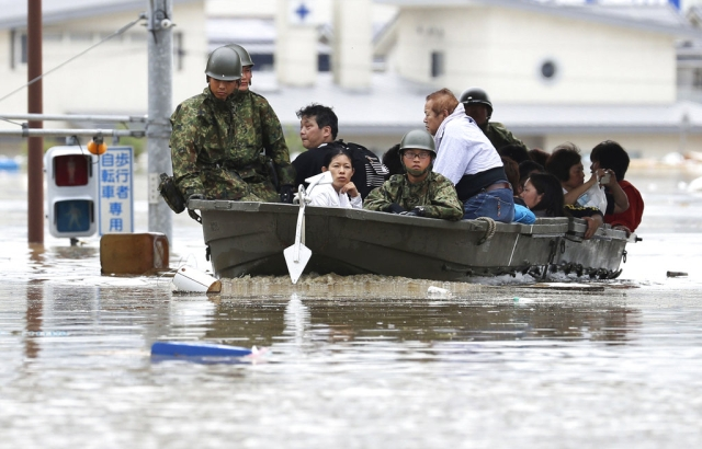 Japan's Ground Self-Defence Force members use a boat to evacuate residents from a flooded area in Kurashiki.