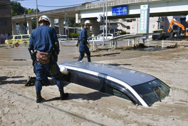 A police officer looks into a car buried in mud during a search operation in the aftermath of heavy rains in Kure, Hiroshima prefecture, southwestern Japan, on Wednesday, 11 July.