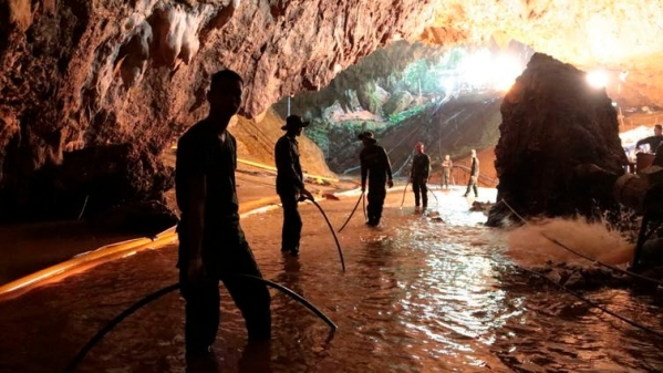 Thai rescue teams arrange a water pumping system at the entrance to the flooded cave complex.