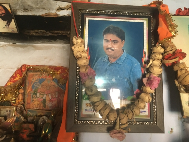 A picture of diamond polisher Bharatbhai Rathod who committed suicide last year hangs at his home in Damrala village in Bhavnagar, India, 31 January, 2018.
