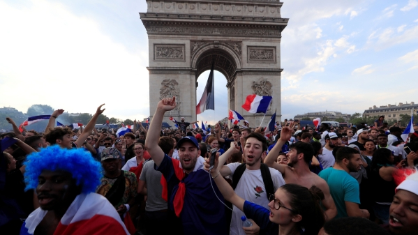 French fans celebrate on the Champs-Elysees avenue near the Arc de Triomphe after France defeated Croatia in the FIFA World Cup final on Sunday.