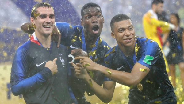 Antoine Griezmann (L) celebrates France's World Cup win with Paul Pogba (C) and Kylian Mbappe (R).