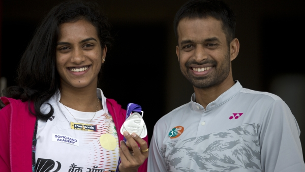Indian Badminton player P. V. Sindhu displays her medal, with her coach Pullela Gopichand standing beside her, during a press conference in Hyderabad, India, Tuesday, Aug. 7, 2018. Sindhu won the silver medal at the BWF World Championships in Nanjing, China.