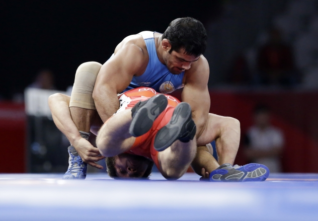 India's Sushil Kumar in blue and Bahrain's Adam Batirov in red compete during Men's freestyle 74 kg wrestling at the 18th Asian Games in Jakarta, Indonesia.