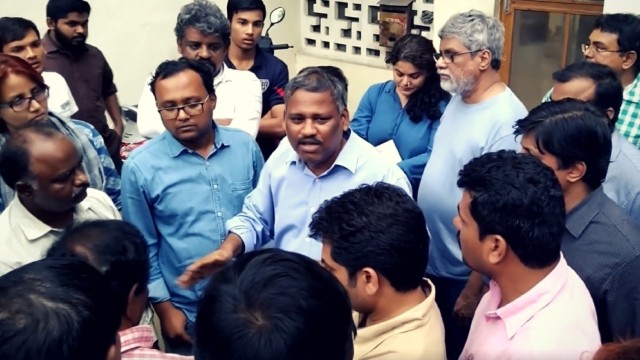 After the raid: Prof K Satyanarayana speaks to his friends outside his Hyderabad residence.