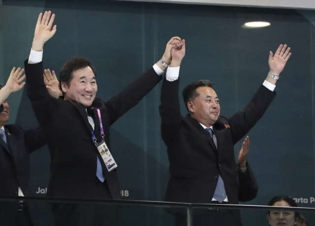 South Korean Prime Minister Lee Nak-yon (L), North Korean Vice Premier Ri Ryong Nam (R) join hands and wave during the opening ceremony.