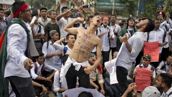 Bangladeshi students shout slogans and block a road during a protest in Dhaka on 4 August.