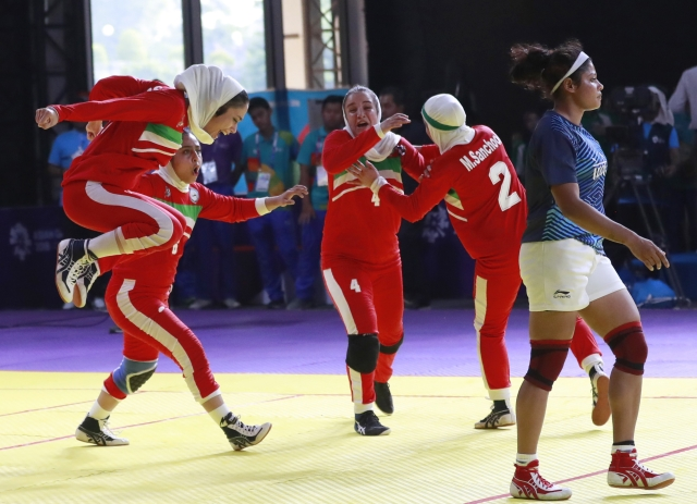 Iran's team, in red, react after defeating India in the women's kabaddi gold medal match at the 18th Asian Games in Jakarta, Indonesia.