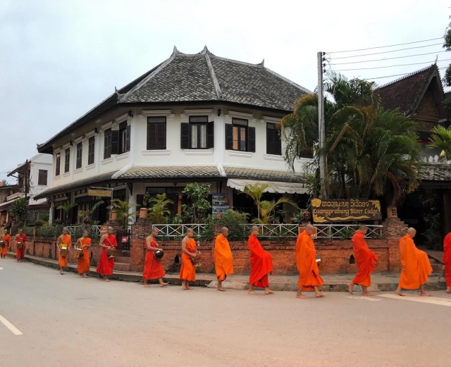 Locals shower the monks with rice, fruits and traditional sweets.