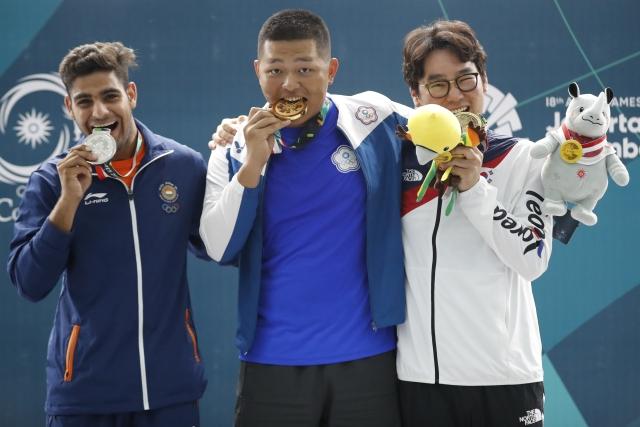 From left to right, silver medalist India's Lakshay, gold medalist Taiwan's Yang Kunpi and bonze medalist South Korea's Ahn Daemyeong celebrate with their medals during the awards ceremony of the trap men shooting event.