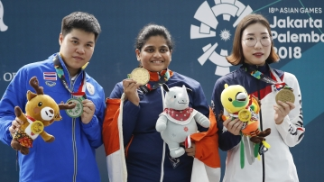 Silver medalist Thailand's Naphaswan Yangpaiboon, left, gold medalist India's Rahi Jeevan Sarnobat, center, and bonze medalist South Korea's Kim Minjung display their medal the final round of the 25m pistol women's shooting event at the 18th Asian Games in Palembang, Indonesia, Wednesday, Aug. 22, 2018.