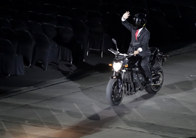 President Joko Widido arrives on a motorbike to the venue of Gelora Bung Karno Stadium.