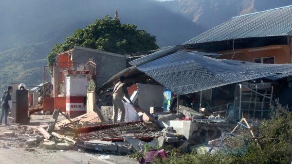 Indonesian men inspect buildings damaged by earthquake in Sembalun, on Lombok Island, Indonesia