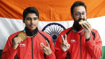 Bonze medalist India's Abhishek Verma, right, and gold medalist India's Saurabh Chaudhary, poses for photographer with India national flag after the 10m air pistol men's final shooting event during the 18th Asian Games.