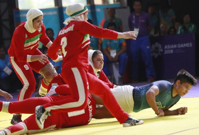 India's Sakshi Kumari, in blue, is caught by Iran's team during the women's Kabaddi gold medal match at the 18th Asian Games in Jakarta.