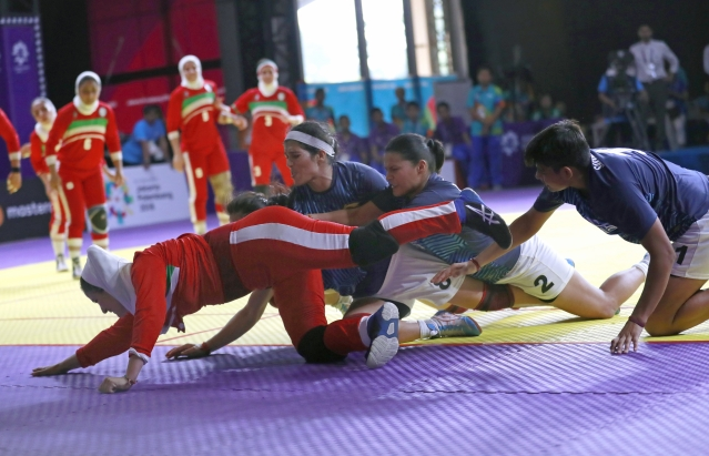 Iran's Saeideh Jafarikoochi, in red, tries to stretch to the line.