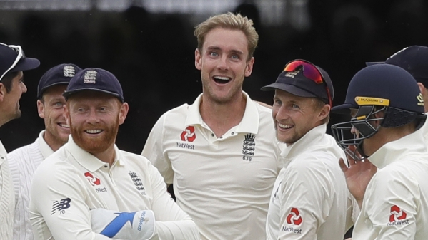 England's Stuart Broad, centre, stands with his team as India's Dinesh Karthik leaves the pitch during the fourth day of the second test match between England and India at Lord's cricket ground in London, Sunday, Aug. 12, 2018.