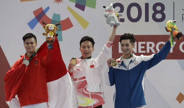 Gold medalist Peiyuan Sun of China, center, Silver medalist Edgar Marvelo of Indonesia, left, and Bronze medalist Tsemin Tai of Taiwan raise their medals during ceremonies for the Wushu men's Changquan games at the 18th Asian Games in Jakarta, Indonesia on Sunday, Aug. 19, 2018.
