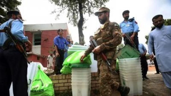 File photo of security officials guarding ballot boxes and voting materials at a distribution center in Islamabad.