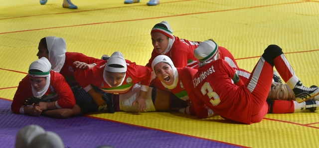 Iranian women's kabaddi team members tackle down an Indian raider.