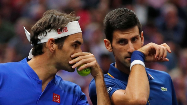 Team Europe's Roger Federer, left, whispers to Novak Djokovic during a men's doubles tennis match against Team World's Jack Sock and Kevin Anderson at the Laver Cup.
