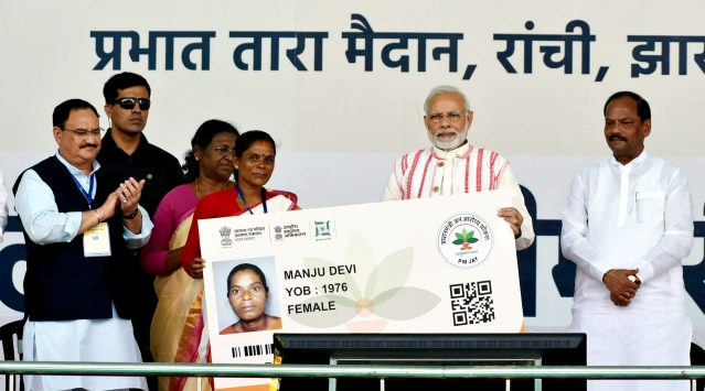 "Prime Minister Narendra Modi presents a health insurance card to a beneficiary during the inauguration of ""Pradhan Mantri Jan Aarogya Yojna"" in Ranchi."