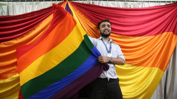 A man poses with the LGBTQ flag following Supreme Court's verdict.