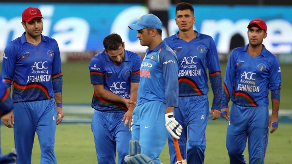India's Mahendra Singh Dhoni, third left, leaves the field after losing his wicket as Afghanistan's Javed Ahmadi.