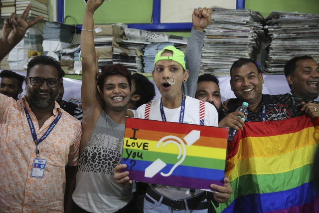 Activists posing with the posters and the LGBTQ flag in Mumbai.