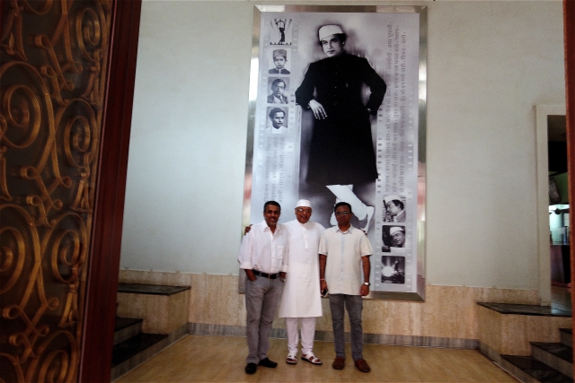 Kiran Shantaram (centre), flanked by his sons Rahul (left) and  Chaitanya in front of Shantaram's photograph.