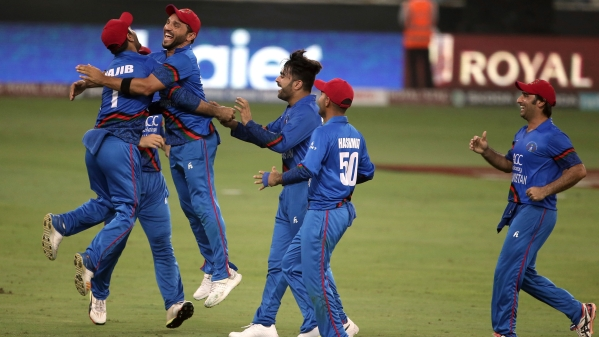 Afghanistan cricketers celebrate after drawing with India in their final Super Four match.