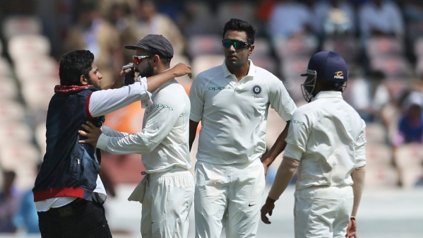 A fan hugs cricketer Virat Kohli after running into the field disrupting play on the first day of the second cricket test match between India and West Indies in Hyderabad.