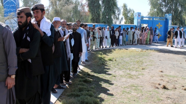 Afghan men line up to cast their votes, outside a polling station during the Parliamentary election in Helmand province, south of Afghanistan, Saturday, Oct. 20, 2018.