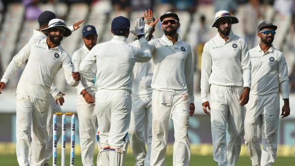 Virat Kohli celebrates a wicket with his teammates.
