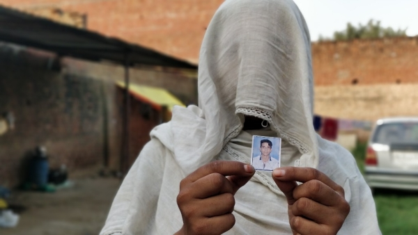 Mustakeen's wife holds a picture of her slain brother-in-law, Naushad.