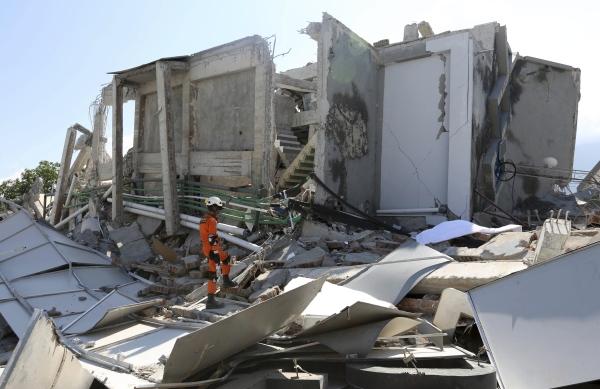 A rescuer inspects the damage of Roa-Roa Hotel following a massive earthquake and tsunami in Palu.